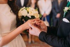 把圆环放的时髦的新郎在他典雅的新娘的手指上在婚礼 免版税图库摄影