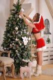 把圣诞节装饰品放的性感的圣诞老人女孩在树上 免版税库存照片