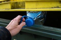 把在一个黄绿色垃圾桶的人的手塑料瓶扔出去-为自然回收 库存图片