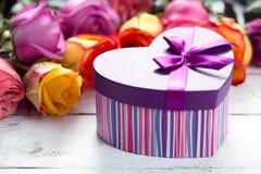 把在最前方,紫色和黄色玫瑰的礼物装箱在木桌上 免版税库存照片