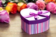 把在最前方,紫色和黄色玫瑰的礼物装箱 库存图片