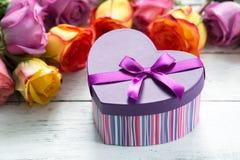 把在最前方,紫色和黄色玫瑰的礼物装箱 免版税库存图片