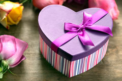 把在木桌上的当前,黄色和紫色玫瑰装箱 免版税库存图片