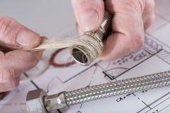 把大麻纤维放的水管工在螺纹上 免版税图库摄影