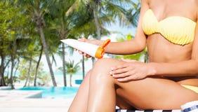 把太阳保护奶油放的女孩在海滩睡椅上 库存照片