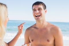 把太阳奶油放的妇女在男朋友鼻子上 图库摄影