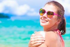 把太阳奶油放的心形的太阳镜的少妇在肩膀上 库存图片