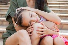 把头放的小女孩在母亲` s膝盖上 免版税库存照片