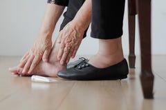 把奶油放的年长妇女在圆鼓的脚上在被投入的鞋子前 免版税库存图片