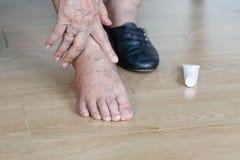 把奶油放的年长妇女在圆鼓的脚上在被投入的鞋子前 库存照片