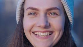 把她的头、神色照相机和笑变成一个年轻美丽的绿眼的深色的女孩的妇女画象 影视素材