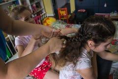 把她的朋友编成辫子的母亲教的少女头发 免版税库存图片