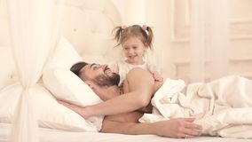 把她的父亲吵醒的小女孩与在面颊的一个亲吻 股票视频