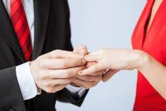 把婚戒放的人在妇女手上 免版税库存照片