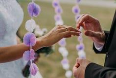 把婚戒放的人的图片在妇女手上 图库摄影