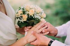 把婚戒放的人的图片在妇女手上 库存照片
