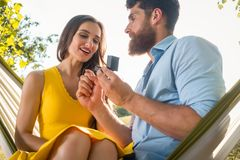 把定婚戒指放的愉快的人在女朋友的手指上  免版税库存照片