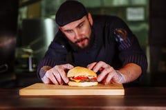 把小圆面包放的厨师在上面上,做顾客定货的他牛肉汉堡 库存照片