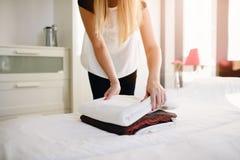 把干净的新鲜的毛巾放的旅馆佣人在床上 免版税库存图片