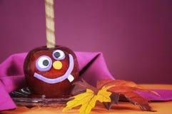 把戏或款待万圣夜特写镜头的愉快的微笑的疯狂的面孔红色奶糖苹果糖果 免版税库存照片