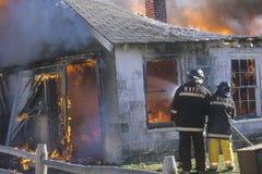 把房子放的消防员在火上 免版税库存照片