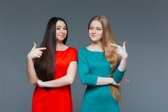 把手指指向的两个愉快的女朋友彼此 免版税库存图片