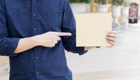 把手指指向的偶然人空白的笔记本在晴天 免版税库存图片
