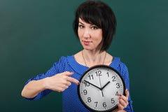 把手指指向的妇女手表,摆在粉笔板、时间和教育概念,绿色背景,演播室射击 库存图片