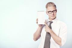 把手指指向的微笑的生意人空白笔记本。 库存图片