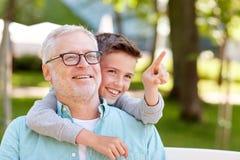 把手指指向的祖父和男孩夏天公园 免版税库存图片