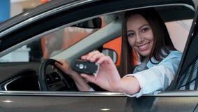 把握关键对新的汽车自动和微笑对照相机的年轻女人 股票视频