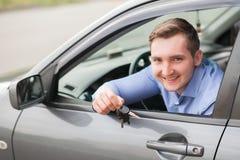 把握关键的愉快的年轻人对新的汽车 免版税库存图片
