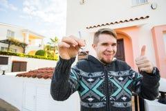 把握在房子的年轻人房子关键塑造了在一个新的家前面的keychain 免版税库存图片