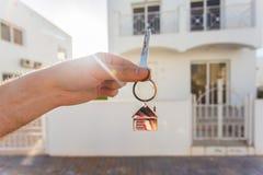 把握在房子的房子关键塑造了在一个新的家前面的keychain特写镜头 实际概念的庄园 免版税库存图片