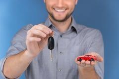 把握在蓝色背景的愉快的人汽车关键 库存图片