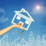 把握房子象和关键的手 天空背景 免版税图库摄影