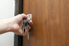 把握捆绑不同的关键的手的特写镜头在钥匙hol中 免版税库存照片