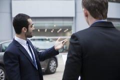 把握汽车关键和卖汽车的汽车推销员对一个年轻商人 免版税库存照片