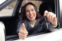 把握汽车关键和显示赞许的妇女 免版税库存图片