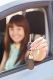 把握汽车关键的愉快的妇女 免版税库存照片