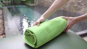 把新鲜的清洁毛巾放的妇女在躺椅上在水池附近在旅馆 免版税库存照片