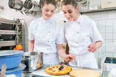 把果子放的妇女在蛋糕上在酥皮点心面包店 免版税库存照片