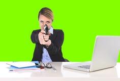 把枪指向的女实业家在独裁的态度色度钥匙的办公桌 库存照片