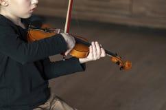 把柄举行小提琴 男孩运载的小提琴 弹小提琴,有天才的小提琴球员的年轻男孩 hornsection仪器音乐零件萨克斯管 免版税库存照片