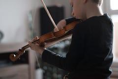 把柄从后面射击的举行小提琴 小男孩运载的小提琴 弹小提琴,有天才的小提琴球员的年轻男孩 音乐 免版税图库摄影