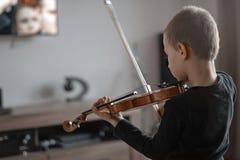 把柄从后面射击的举行小提琴 小男孩运载的小提琴 弹小提琴,有天才的小提琴球员的年轻男孩 音乐 免版税库存照片