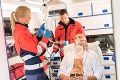 把氧气面罩放的医务人员在耐心的救护车上 免版税库存照片