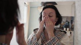 把润湿的奶油放的美丽的健康妇女画象在面孔上 股票录像