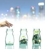 把混合硬币和种子放的手在清楚的瓶在都市风景照片上 库存照片