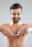 把牙膏放的一个微笑的人的画象在牙刷上 库存图片